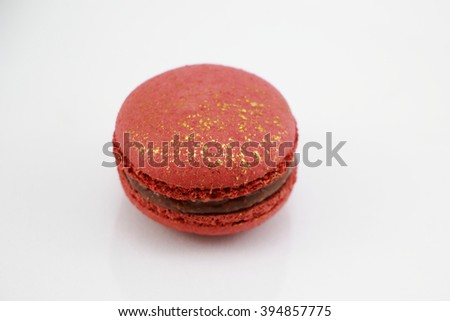 Top view of Impressive a gold-red, large-sized patterned macaron filled with mild sweet lychee ganache , raspberry jelly and chocolate - stock photo