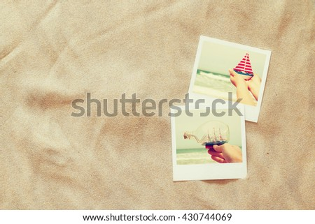 top view of instant photos album on sand background. vintage filtered image
