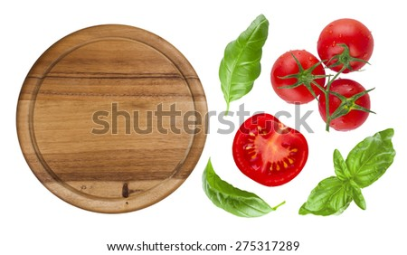 Top view of isolated cutting board with tomato and basil - stock photo