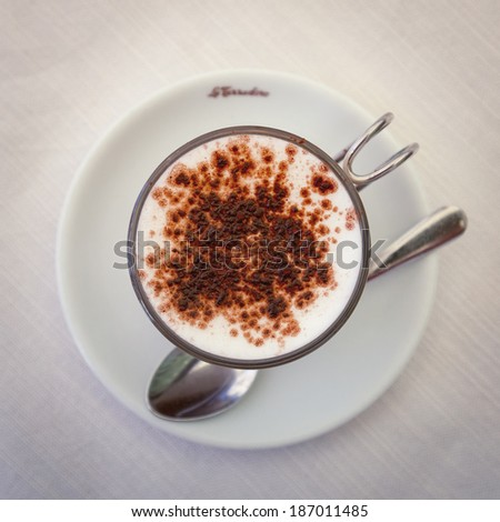 Top view of Italian coffee latte or cappuccino drink with a white saucer and spoon on a plain table. / Italian Coffee Latte - stock photo