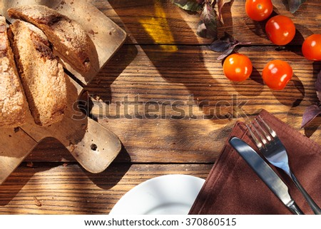 Top view of italian food on wooden table - bread, olive oil and tomatoes with basil