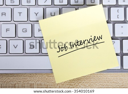 Top view of Job Interview sticky note pasted on the keyboard. - stock photo