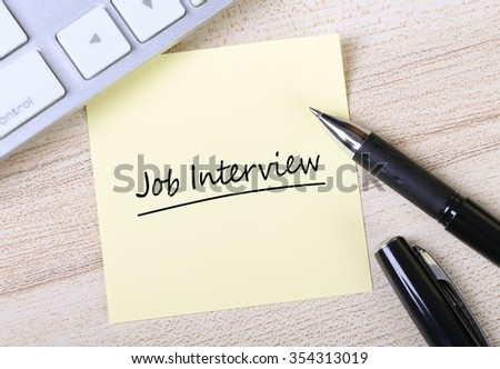 Top view of Job Interview sticky note pasted on the wooden desk with keyboard and pen aside. - stock photo