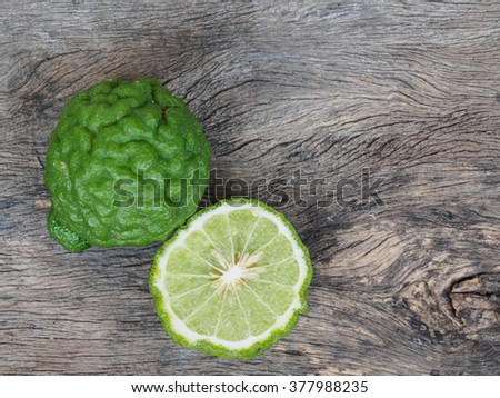 Top view of kaffir lime slice on rustic wooden background with copy space - stock photo