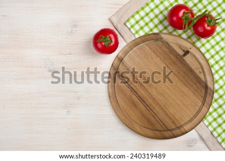 Top view of kitchen cutting board over wooden background - stock photo