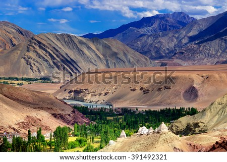 Top view of ladakh landscape, green valley field with barren mountains around, play of light and shadow on mountains, Leh, Ladakh, India - stock photo