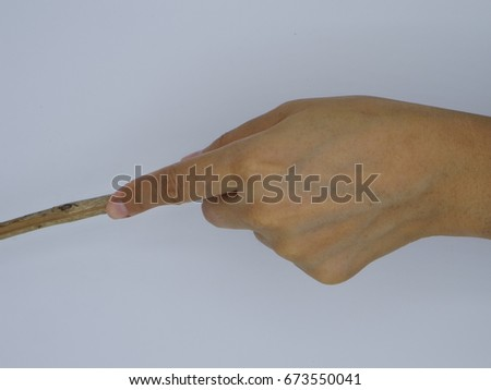 Top view of left hand holding a wooden stick