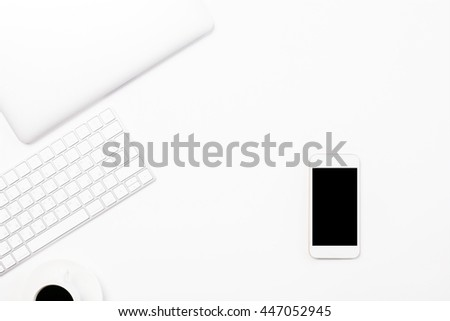Top view of light desktop blank smartphone, coffee cup, computer keyboard and closed laptop. Mock up - stock photo