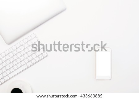 Top view of light desktop blank white smartphone, coffee cup, computer keyboard and closed laptop. Mock up - stock photo