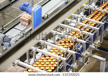 Top view of line with bottles of fresh light beer with red caps in modern beer factory. - stock photo
