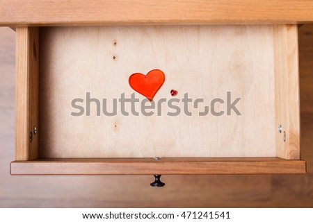 top view of little and big red hearts in open drawer of nightstand
