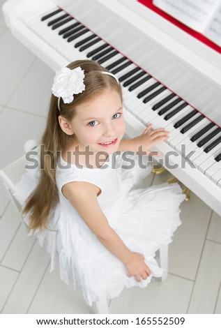 Top view of little girl in white dress playing piano. Concept of music study and creative hobby - stock photo