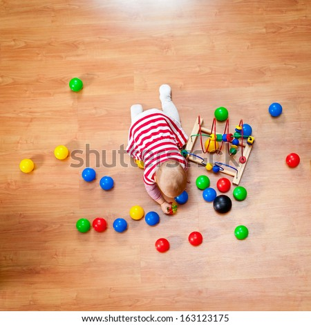 Top view of little girl playing on the floor - stock photo