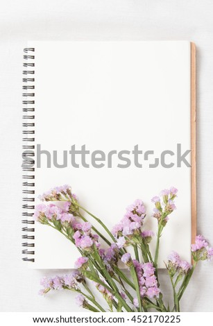 Top view of little plant with flowers on blank notebook on white fabric workspace background. - stock photo