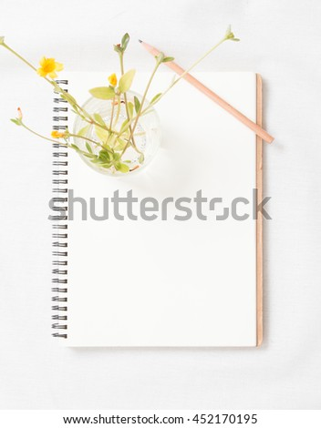 Top view of little plant with flowers on blank notebook on white fabric workspace background. Focus notebook. - stock photo