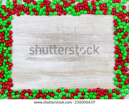 Top view of little red and green candies forming a border on rustic wooden boards