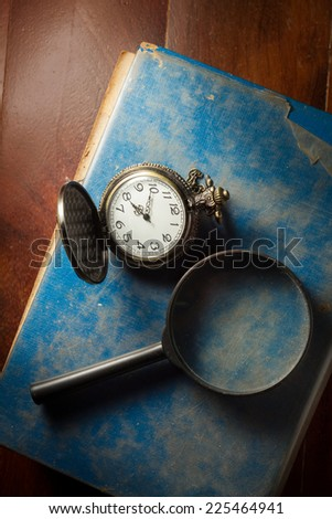 Top view of magnifier and pocket watch on books. - stock photo