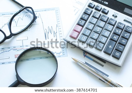 Top view of Magnifying glass with calculator ,eyeglasses and pen on stock graph