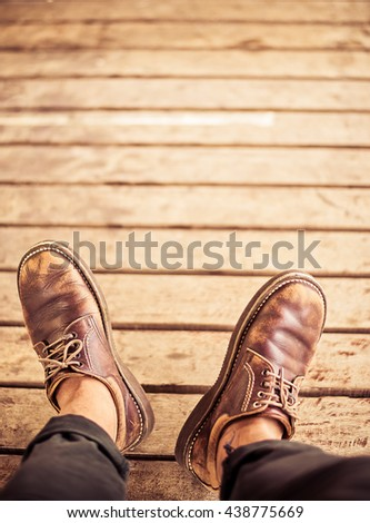Top view of Male feet in old leather shoes on wood add vintage color - stock photo