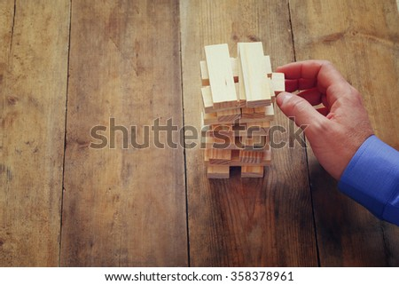 top view of male hand placing wooden block on a tower. planing and strategy concept  - stock photo