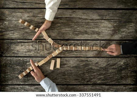 Top view of male hand pushing dominos placed in Y shape knocking them down and two other hands stopping them each on one side. Conceptual of crisis management in business. - stock photo