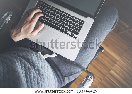 Top view of male hands using modern laptop, close up of young man working at home and using notebook computer, man's hand using technology in interior - stock photo