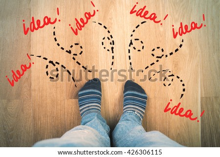 Top view of male legs and feet in socks on wooden floor with sketches around. Idea concept - stock photo