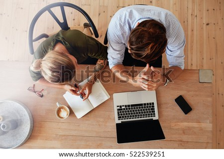 Top view of man and woman sitting at table and working. Two people working together on laptop.