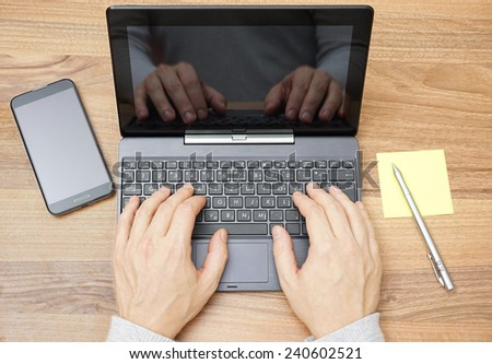 Top view of man hands working on laptop or tablet pc on wooden desk - stock photo