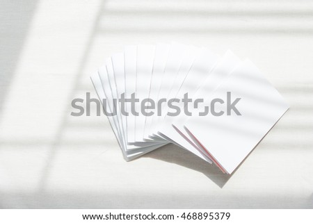 Top view of many blank white notebooks on white fabric background. Shadow.