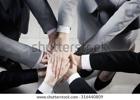 Top view of many businesspeople with hands joined in stack - stock photo
