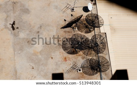 Top view of many satellite dish on rooftop of building.