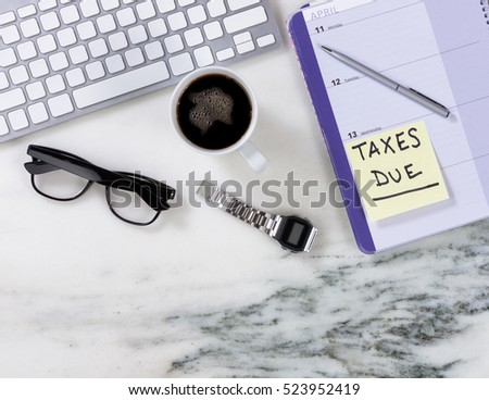 Top view of marble office desktop with computer keyboard, coffee, calendar, pen, watch and reading glasses. Tax planning concept.