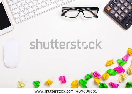 Top view of messy white office desktop with crumpled paper, glasses, calculator, computer mouse, keyboard and smart phone. Mock up - stock photo