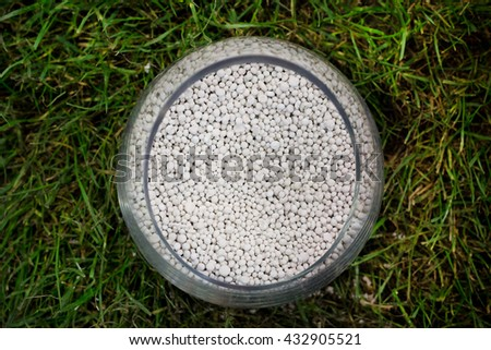 Top view of mineral fertilizer for soil in glass pot in the grass - stock photo
