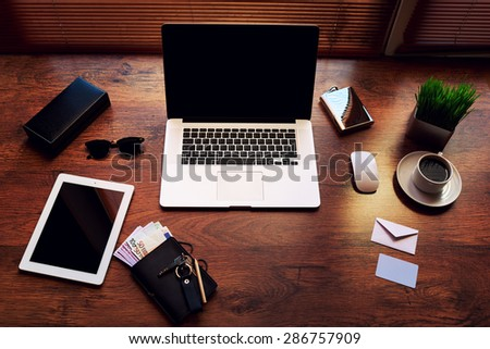 Top view of modern businessman or entrepreneur workspace with style accessories, euro bills, cup of coffee, open laptop computer and digital tablet with white blank copy space screen, filtered image - stock photo
