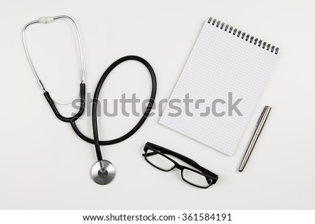 Top view of modern, sterile doctors office desk. Medical accessories on a white background with copy space around products. Photo taken from above. - stock photo