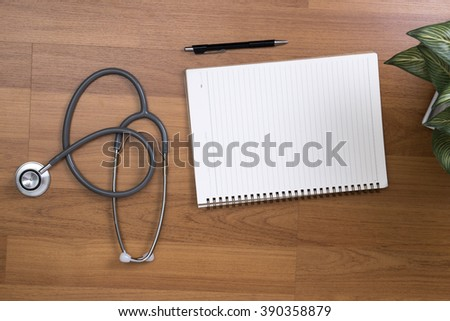 Top view of modern, sterile doctors office desk. Medical accessories on table  with book copy space - stock photo