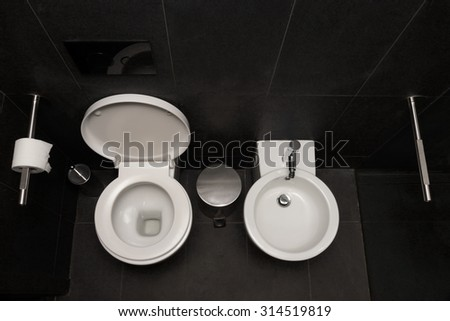 Top View Of Modern Toilet Bowl, Bidet And Toilet Paper In The Black Room - stock photo