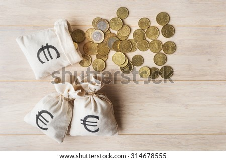 Top view of money bags and euro coins over wooden background - stock photo