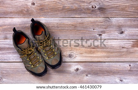 Top view of new hiking shoes on rustic wooden boards