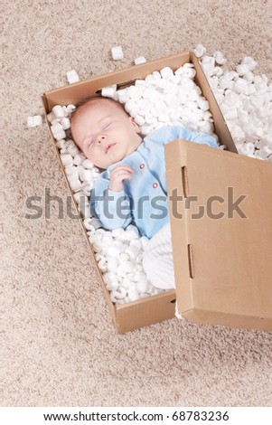 Top view of newborn baby lying in open post box with filler. Little baby sleeping in box and waiting for his parents while lying on comfortable carpet. - stock photo
