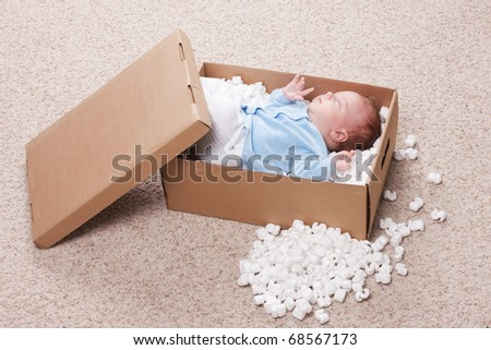 Top view of newborn baby represented in open post box with filler. Small baby sleeping. Newborn boy is going to be delivered to his parents somewhere.
