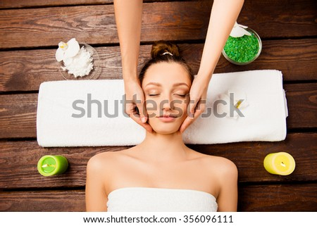 Top view of nice young woman laying in spa salon relaxing having spa procedures - stock photo