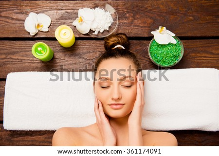 Top view of nice young woman laying in spa salon relaxing with closed eyes - stock photo