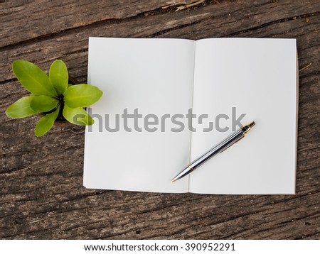 top view of note book and pen on wooden background with copy space - stock photo