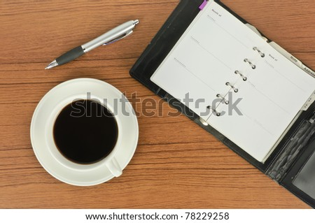 Top view of notebook and pen with coffee on table