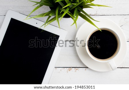 Top view of office desk, a cup of coffee and tablet computer