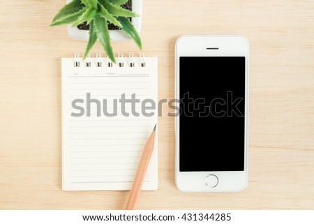 Top view of office desk table with mobile phone, spiral notebook, pencil, and small tree in a white pot on wood table - stock photo