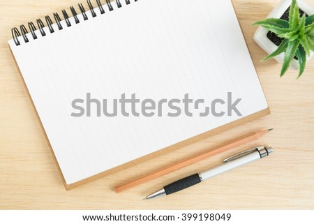 Top view of office desk table with open spiral notebook, pencil, and small tree in a white pot on wood table - stock photo